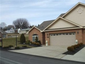 Front view of a garage and driveway in townhome community.