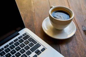 An open laptop sitting next to a cup of coffee on a wooden table.