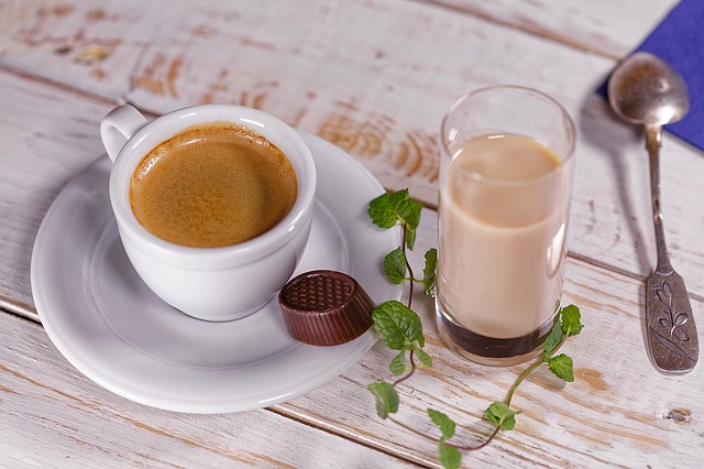 A latte in a ceramic mug sitting on a wooden table.