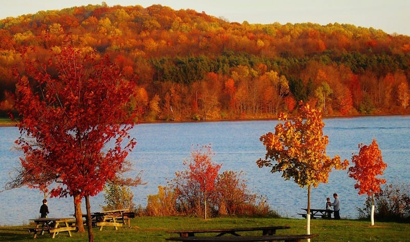 A lake in the foreground with red and yellow fall trees in the background on a hill.