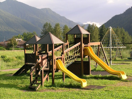 A wooden play structure with two yellow slides and a swingset.