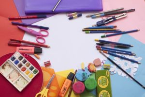 Colorful construction paper surrounded by art supplies, including watercolors, pencils, safety scissors, and paints.