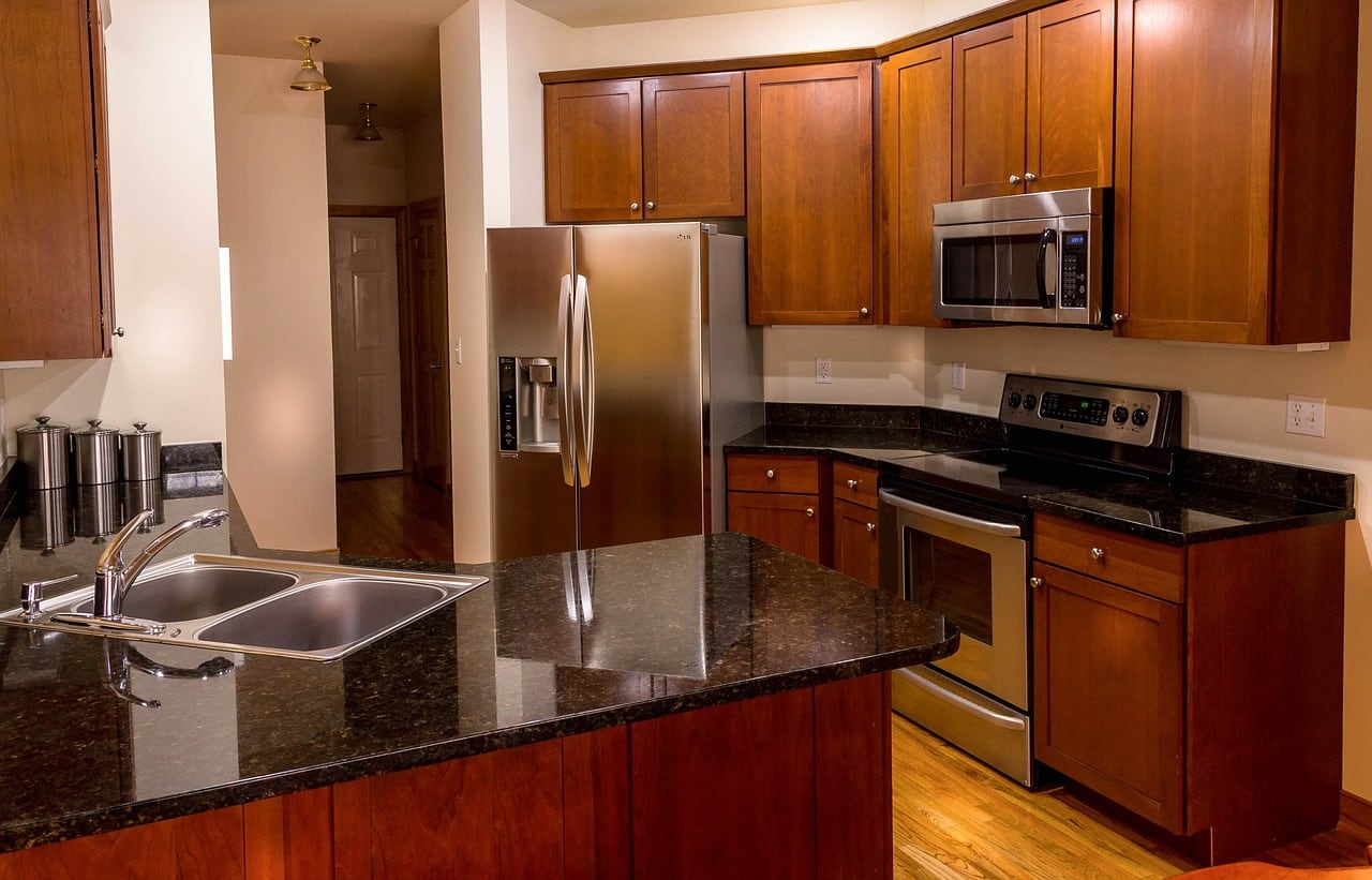 A large kitchen with granite countertops and cherry cabinets.