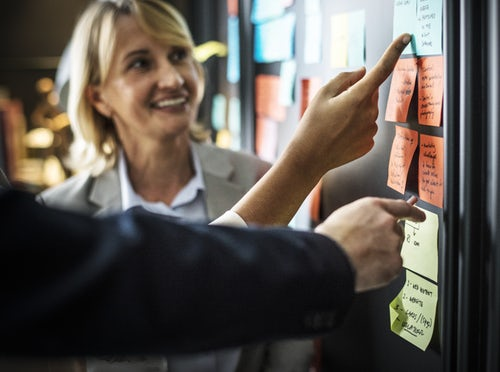 People pointing at sticky notes.